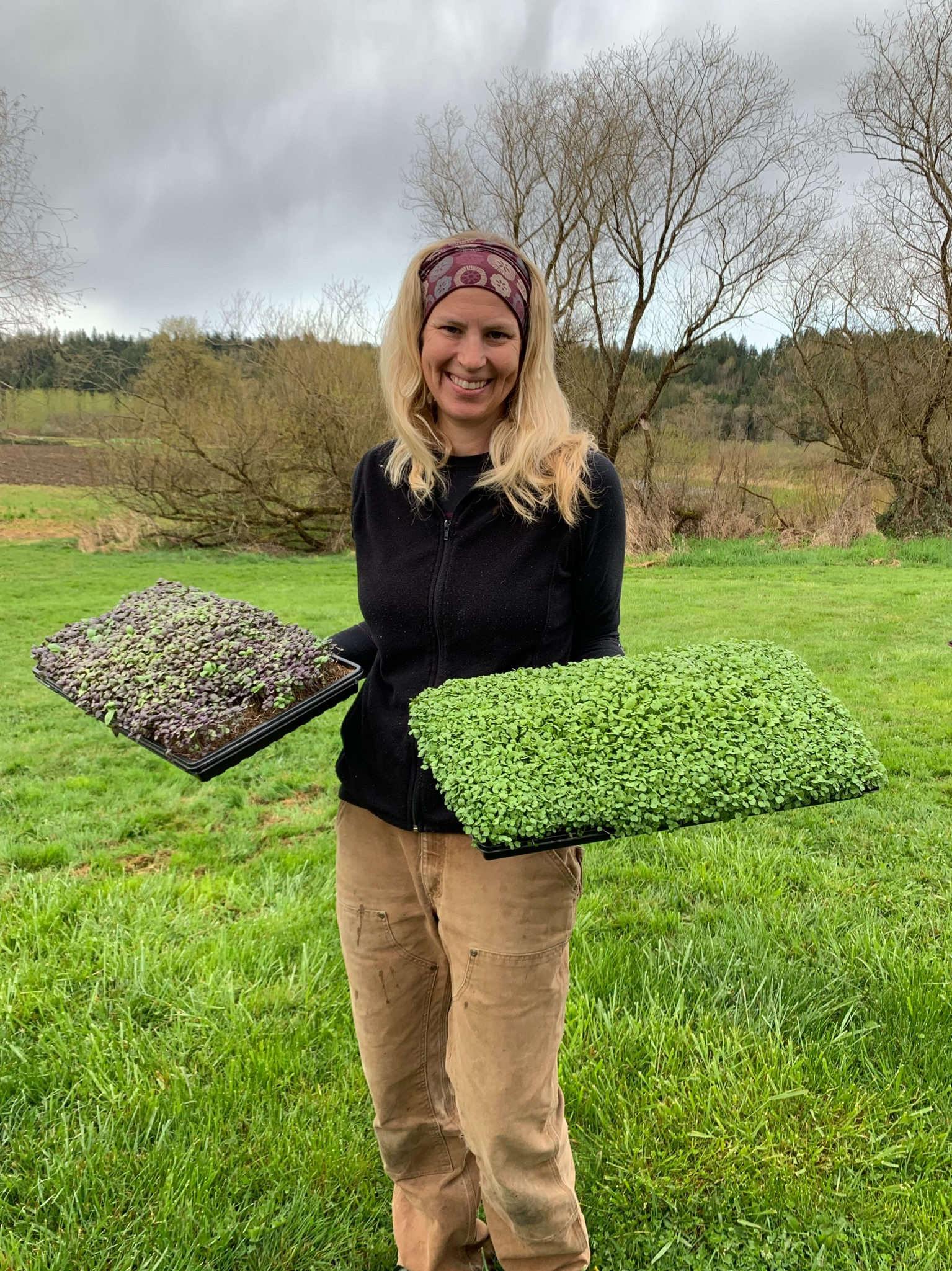 Hand-Grown Greens owner with microgreen trays